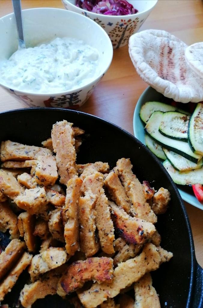 Vegaanisen pitan ainekset seitan, tzatziki ja vihannekset pöydällä