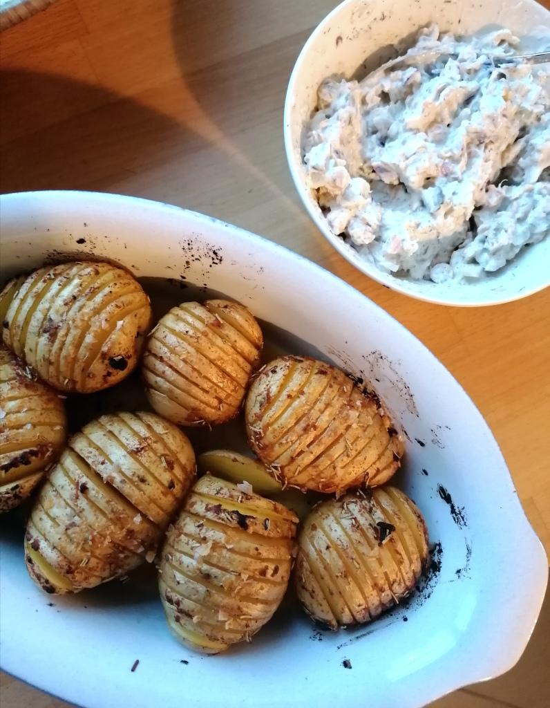 Vegaaniset uuniperunat uunivuoassa pöydällä ja kylmä kikhernekastike