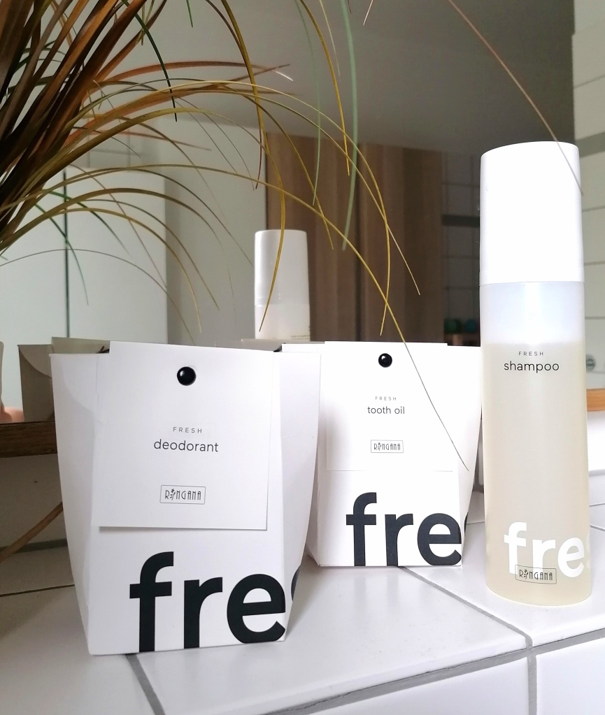 Ringana-luonnonkosmetiikkaa, shampoo, deodorantti ja hammasöljy kylpyhuoneen hyllyllä