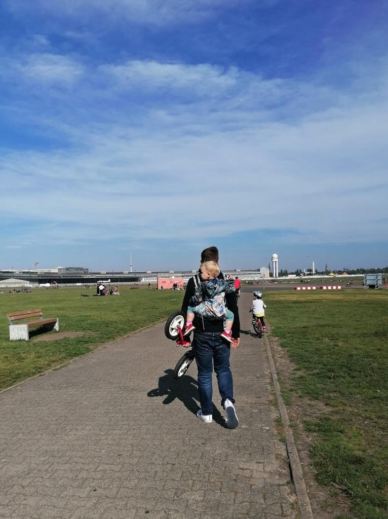 Expat-perhe kävelyllä Berliinin Tempelhofin kentällä aurinkoisena syyspäivänä