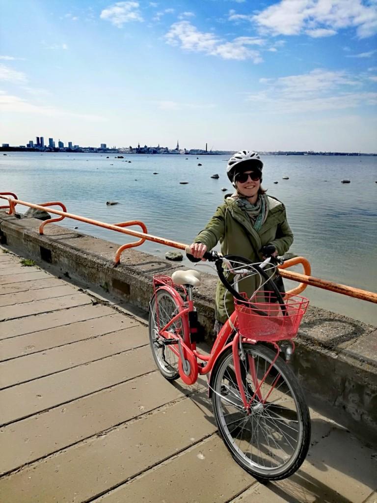 Ulkosuomalainen nainen Tallinnassa meren rannassa pyörän kanssa.
